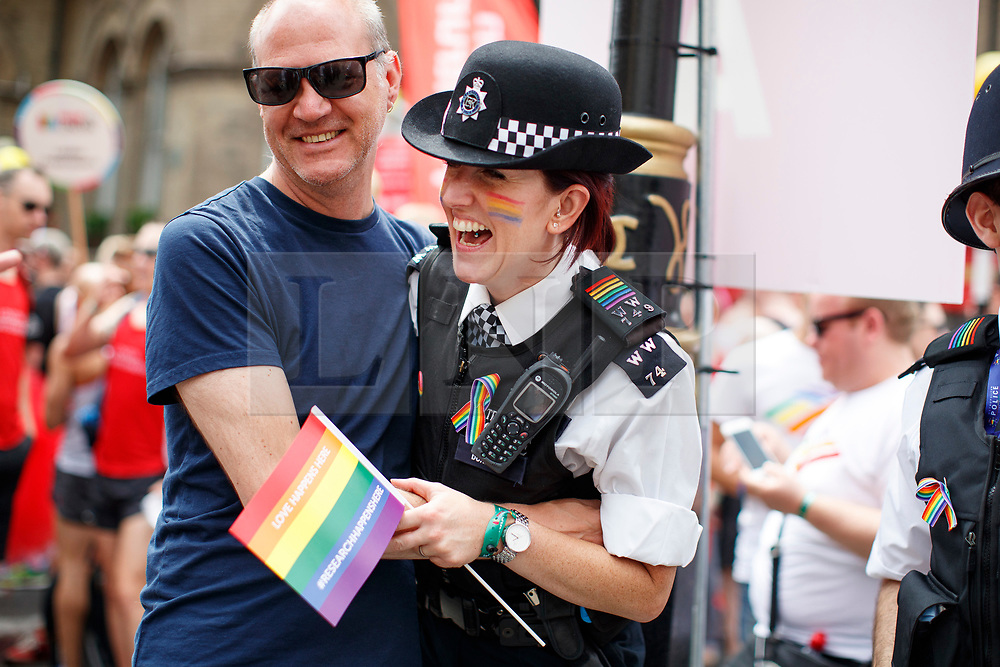 © Licensed to London News Pictures. 08/07/2017. London, UK. Police officers pose with people marching at The Pride in London Festival in central London on  Saturday, 8 July 2017 to celebrate all aspects of the LGBT+ community. The Parade attracts an estimated crowd of 1 million people and around 26,500 people take part in the march every year. Photo credit: Tolga Akmen/LNP