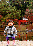 A little girl posing for the camera in front of a Japanese garden located in the city of Nara, Japan.