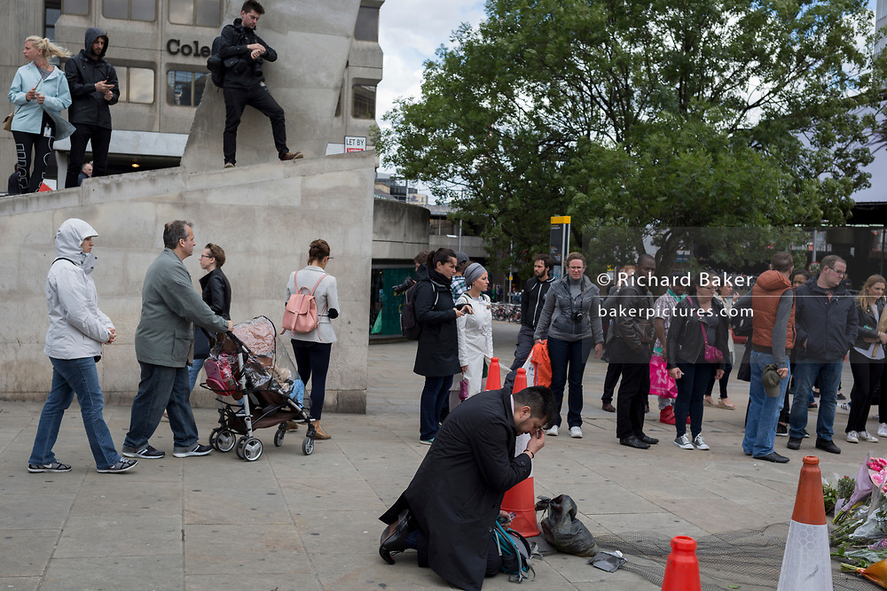 Three days after the terrorist attack in which 7 people died and many others suffered life-changing injuries on London Bridge and Borough Market, a gentelman bows to pray near a shrine of flower tributes which has grown near the crime scene site, on 6th June 2017, on London Bridge, in the south London borough of Southwark, England. City commuters now back at work walk respectfully and quietly past the floral memorial at the plinth marking the southern boundary of the City of London, the capital's financial district.