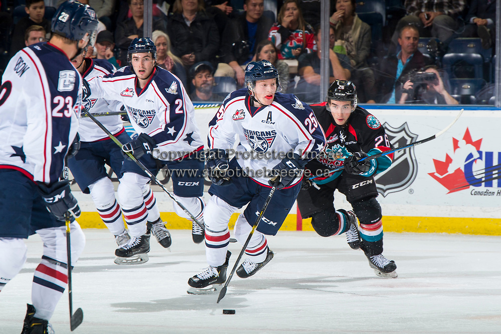 KELOWNA, CANADA - OCTOBER 13:  Liam Kindree #26 of the Kelowna Rockets back checks Kyle Olson #25 of the Tri-City Americans as he skates with the puck during third period on October 13, 2018 at Prospera Place in Kelowna, British Columbia, Canada.  (Photo by Marissa Baecker/Shoot the Breeze)  *** Local Caption ***