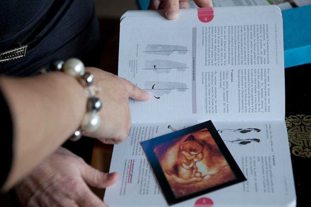 Maria Chevolleau sage femme, en visite à domicile. Pour le suivi de grossesse elle pratique l'examen obstétrical, l'examen des urines, prend la tension, note le poids et explique bilans, échographies tout en donnant des conseils. Créteil, 24 janvier 2013.