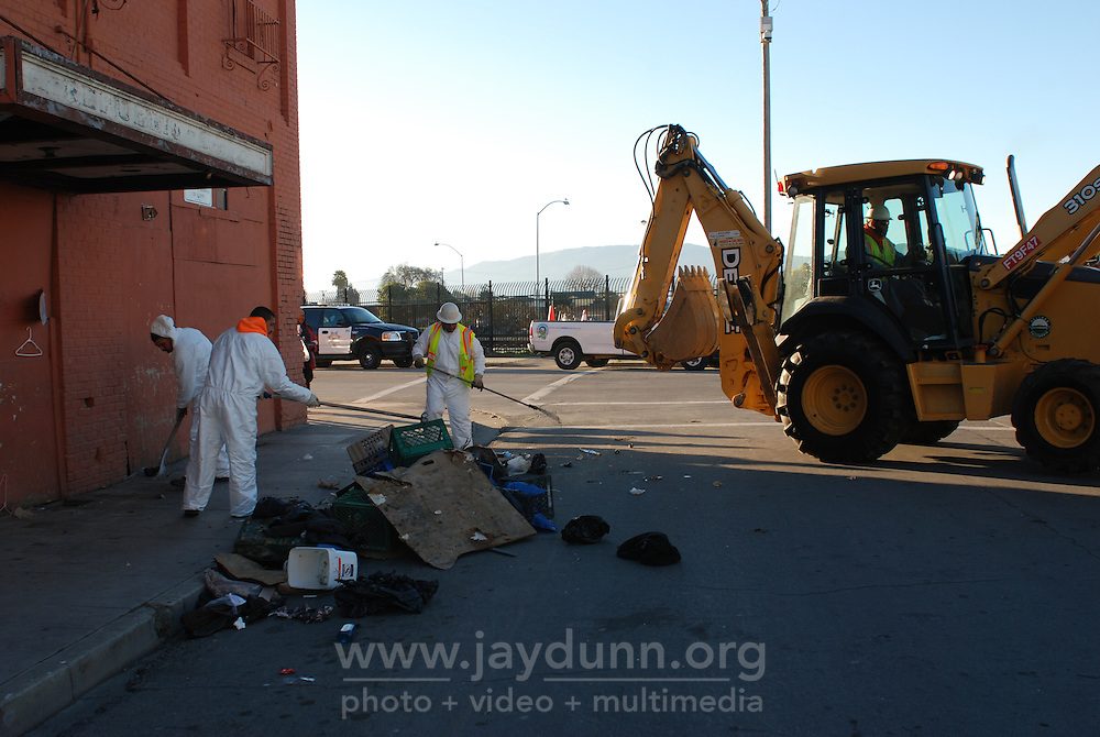 On Thursday, January 31st, 2013, Salinas city workers, health officials and police conducted an early morning sweep of the Chinatown homeless population, removing encampments on the street and in lots between buildings all along Soledad Street. Although ample warning had been given by authorities, a number of homeless were displaced and have now scattered across the city. A fencing company moved in right behind the city's workers, digging postholes, and erecting chain link fencing in sections. Using a front loader, unclaimed possessions were taken away and disposed of over the course of three hours, leaving many people standing about on the street with nowhere to go.