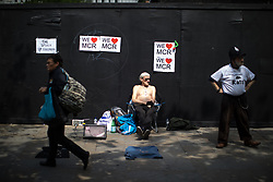 © Licensed to London News Pictures . 25/05/2017 . Manchester , UK . RAY BODDINGTON (76) sunbathes on the pavement in Piccadilly in Manchester City Centre as the city starts to return to normal , following a terrorist attack at an Ariana Grande concert at Manchester Arena that killed twenty two people . Photo credit : Joel Goodman/LNP