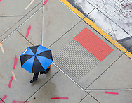 A pedestrian tries to stay dry while walking in downtown South Bend on a soggy afternoon. Tribune Photo/SANTIAGO FLORES