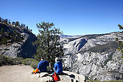 hikers enjoy the view from the top of Half Dome rock at Yosemite national Park, California USA