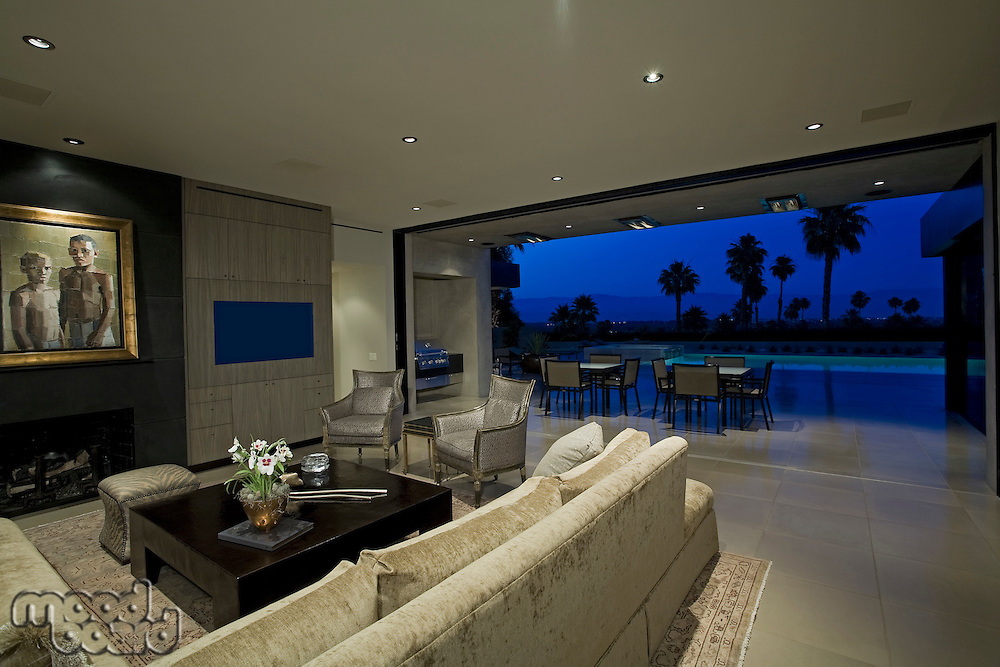 Luxurious interior with view of swimming pool and patio dusk