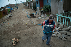 A man distributes water using a hose in the area known as Lomo de Corvina in the district of Villa El Salvador in Lima, Peru. This area has access to water only through one faucet located in the street.