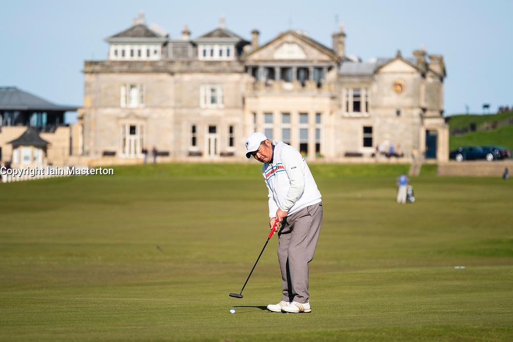 Asian golfer putting on the 17th green ( Road Hole) and  club house of The Royal and Ancient Golf Club (R&A) Old Course in St Andrews, Fife, Scotland, UK.