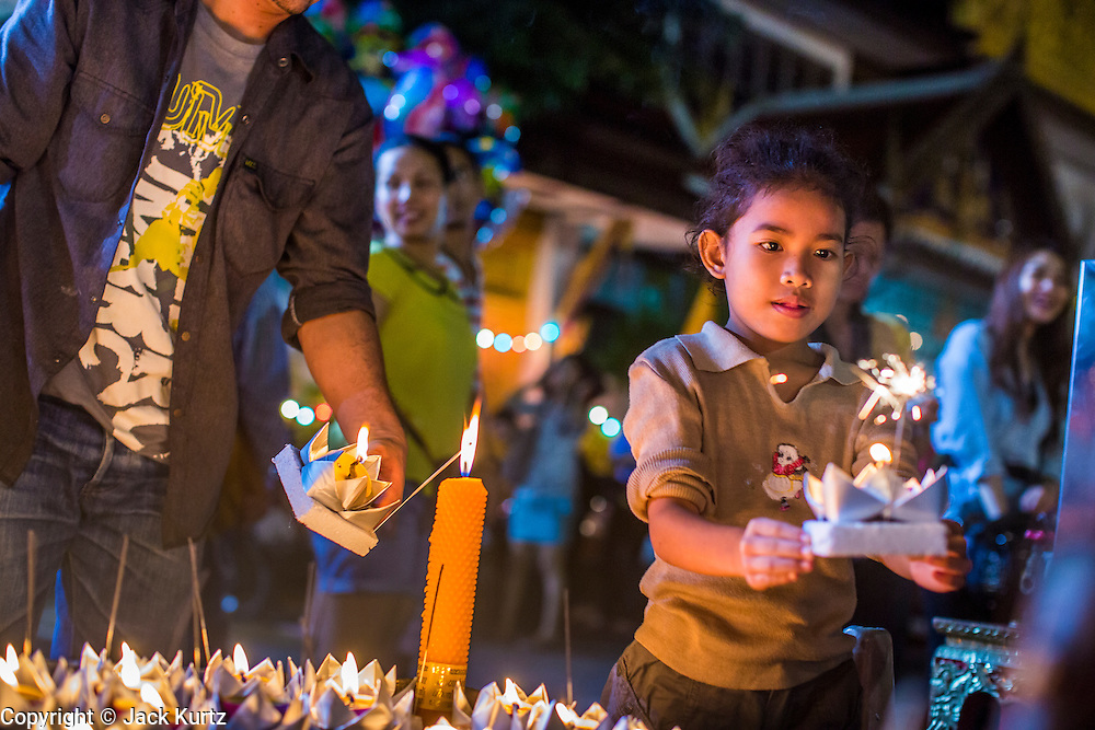 28 NOVEMBER 2012 - BANGKOK, THAILAND:  A girl carries her krathong to a small pool to float it at Wat Yannawa in Bangkok. Loy Krathong takes place on the evening of the full moon of the 12th month in the traditional Thai lunar calendar. In the western calendar this usually falls in November. Loy means 'to float', while krathong refers to the usually lotus-shaped container which floats on the water. Traditional krathongs are made of the layers of the trunk of a banana tree or a spider lily plant. Now, many people use krathongs of baked bread which disintegrate in the water and feed the fish. A krathong is decorated with elaborately folded banana leaves, incense sticks, and a candle. A small coin is sometimes included as an offering to the river spirits. On the night of the full moon, Thais launch their krathong on a river, canal or a pond, making a wish as they do so.   PHOTO BY JACK KURTZ