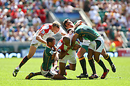 Twickenham, London - Sunday 23rd May 2010: Tom Varndell of England is tackled by three South Africans during the quarter final match (which England lost) during the Emirates London Sevens rugby tournament at Twickenham Stadium, London, UK. (Pic by Andrew Tobin/Focus Images)