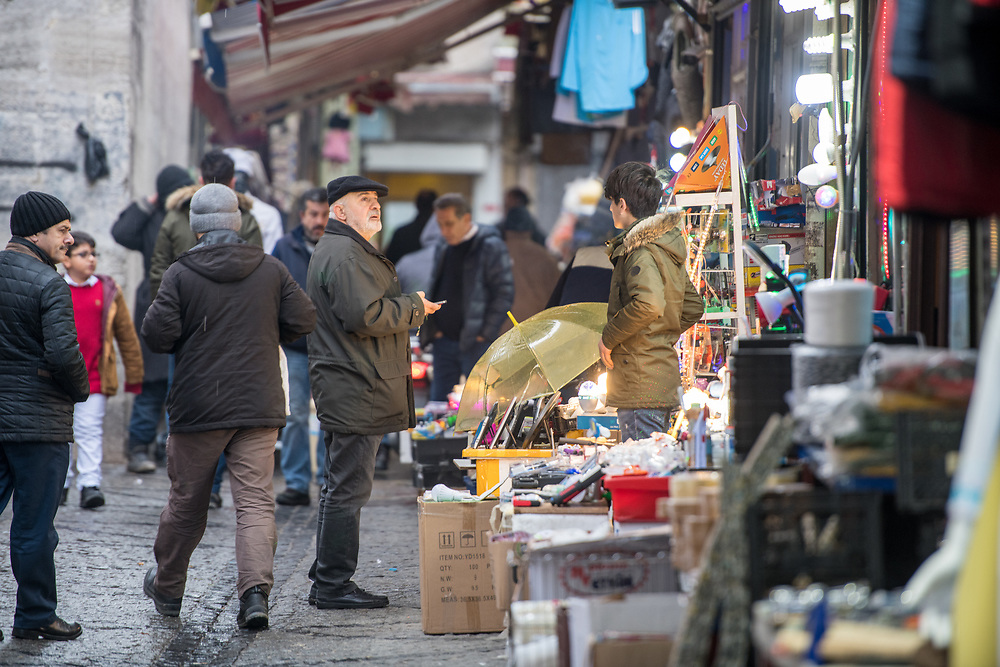 Shoppers walk along street of outdoor marketplace selling various goods, Istanbul, Turkey
