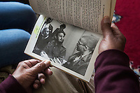 """CASABLANCA, MOROCCO - 14 MAY 2016: Luqman Abdul-Hakeem (82), a close follower of Malcolm X that chauffeured the African American activist around and introduced him to Cuban leader  Fidel Castro in September 1960, shows a picture of him (on the left) with the two leaders published in Rosemari Mealy's book """"Fidel & Malcolm X. Memories of a meeting"""", in his home in Sidi Maarouf, a district of Casablanca, Morocco, on May 14th 2016.<br /> <br /> Born in Cleveland, OH, in 1934, Luqman Abdul-Hakeem was raised in Flushing, Queens, and then moved to Bayside, where he graduated in 1952. He attended the New York Technical University for a few months before enrolling in the Navy, where he stayed for two years. Though he had asked for ship duty, he ended up in Springfield, Mass., and Glennclose, Ill. He moved to Brooklyn when his hitch was done and by 1966 was studying jujitsu and aikido. He met Malcolm X during one of his sermons on 116th street in Harlem, New York, in the late 50's. In 1985, Mr. Hakeem decided to move to Marocco because America wasn't a country where he wanted to raise hois children. He has been teaching aikido in the two dojos he owns in Casablanca until 2014, when he underwent a surgery."""