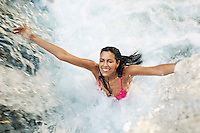 Young woman standing under waterfall with arms outstretched high angle view