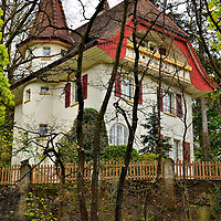 Swiss Home in Bern, Switzerland <br /> This Swiss home with its gabled roof, turret and bright red shutters must have a commanding view of the Old Town of Bern and the Aare River from its balcony.  It sits high on a hill along Feldeggweg.  This photo was taken below along Schwellenmattstrasse.