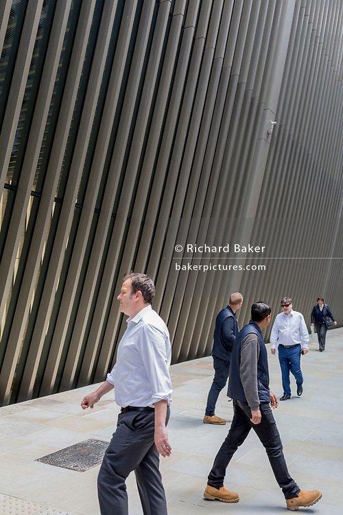 Beneath new architecture, City workers and businessmen walk along Bevis Marks in the City of London, the capital's financial district, on 17th June 2019, in London, England.