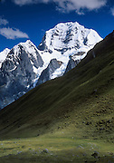 "Trek to see the impressive peak of Siula Grande in the Cordillera Huayhuash, Andes Mountains, Peru, South America. Siula Grande (northeast face, 20,800 feet or 6344 meters elevation) was the subject of the gripping 2003 British docudrama ""Touching the Void."" In 1985, climbers Joe Simpson and Simon Yates scaled the treacherous Siula Grande, one of the last unconquered mountains in the Andes, but after Joe broke his leg, their descent became one of the most amazing survival stories in mountaineering history. This photo shows the northeast face, but they climbed Siula Grande from a valley on the other side (the west face) and descended along the north ridge, on the upper right. The 2003 movie is based upon Joe Simpson's harrowing book, ""Touching the Void: The True Story of One Man's Miraculous Survival."""