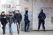 Brussels 23 March 2016.Police officers guard the metro entrance of De Brouckere. Three young guys passing by