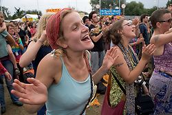 Woman in a crowd listening and dancing to band of musicians playing on stage at the WOMAD (World of Music; Arts and Dance) Festival in reading; 2005,