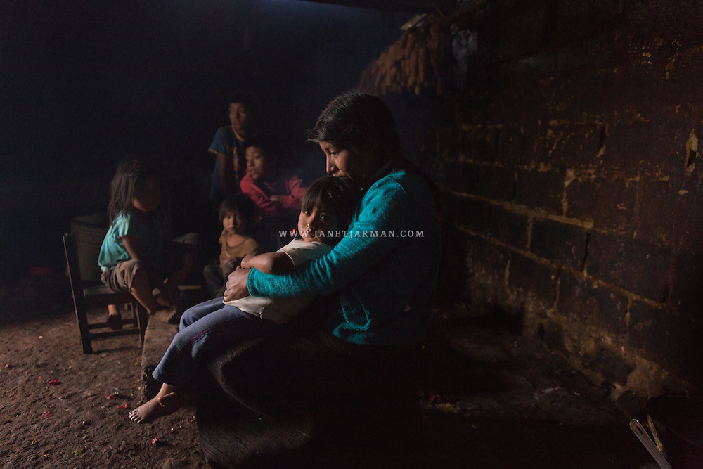 "Carolina Hernández López, 34, takes shelter from torrential rains surrounded by her children, inside their one room home, near San Cristobal de Las Casas in Mexico's Chiapas state. She embraces one of her daughters, Lupita, 3, who suffered a severe burn to her back when she fell into the cooking fire (pictured behind them). Accidents like these are commonplace in Chiapas, the poorest state in Mexico. Residents use open fires to warm their homes and cook their food. Hernandez is grateful to Sergio Castro, who treated her daughter's burn wounds. The revered humanitarian, known by many throughout Chiapas as ""Don Sergio"" has treated burn victims for decades, free of charge."