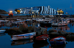 The cruise liner Costa Concordia, which ran aground off the west coast of Italy, is seen outside the harbour at dusk at Giglio island January 27, 2012. Costa Cruises has offered to pay 11,000 euros ($14,500) in compensation to each of the more than 3,000 passengers aboard the ship that capsized near the island of Giglio two weeks ago, Italian consumer groups said on Friday.<br /> REUTERS/Darrin Zammit Lupi (ITALY)