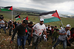 Protesters covered in blood from the casualties sustained from Israeli gunfire at the border fence, climb back up the mountain in Maroun al-Ras.