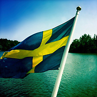 The Swedish flag over a green sea on a sunny day