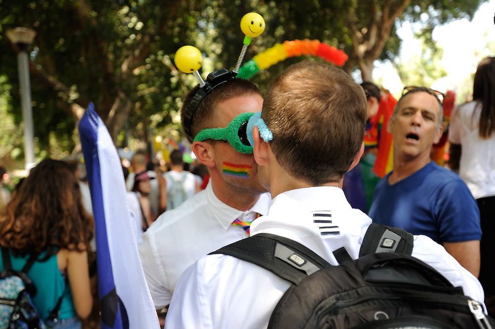 Tel Aviv, Israel - June 13, 2014: A man is watching as two members of the gay comminuty are kissing during the Annual Gay Pride Parade in Tel Aviv on June 13, 2014. More than 100,000 people took part in the Annual Gay Pride Parade in Tel Aviv. Photo by Gili Yaari