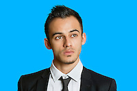 Thoughtful young businessman looking away over colored background