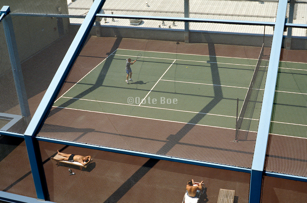 View of people playing tennis and sunbathing