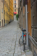 A blue bicycle on a quaint cobblestone street in Gamla Stan, Old Town, Stockholm, Sweden, Europe. This is part of a series. Other views are available. There are so many beautiful narrow streets and alleys in this medieval section of the Swedish capital city.