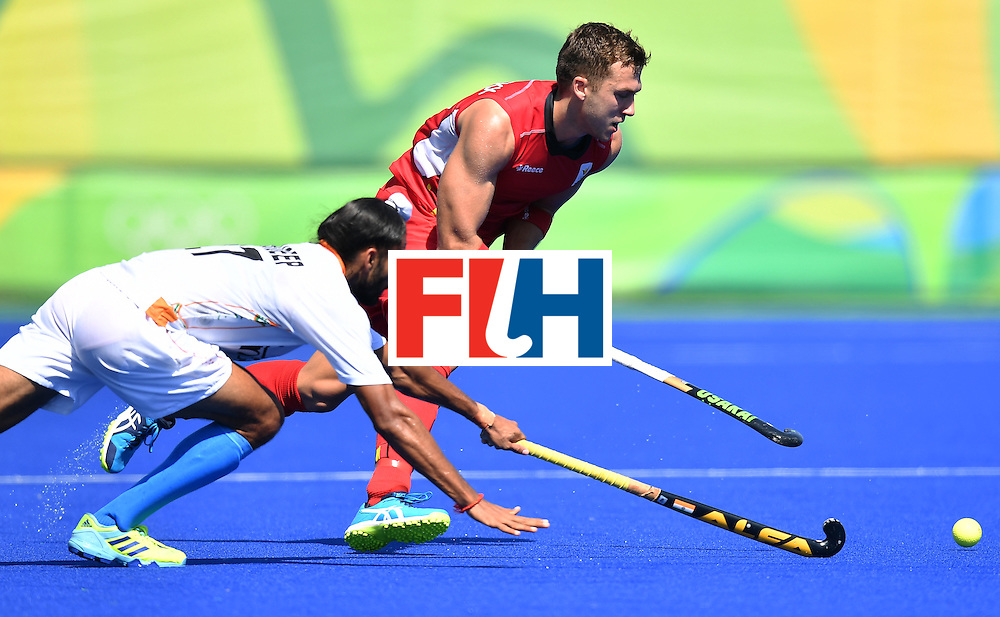 Belgium's Emmanuel Stockbroekx (R) vies with India's Akashdeep Singh during the men's quarterfinal field hockey Belgium vs India match of the Rio 2016 Olympics Games at the Olympic Hockey Centre in Rio de Janeiro on August 14, 2016. / AFP / MANAN VATSYAYANA        (Photo credit should read MANAN VATSYAYANA/AFP/Getty Images)
