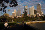 Sydney Sites travel series. Runners early in the morning run through the Sydney Botanical gardens with the Sydney Skyline in the background.
