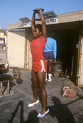 woman in Venice Beach, CA lifting weights in high heel shoes and gym clothes