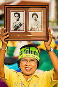 05 MAY 2104 - BANGKOK, THAILAND: A Thai supporter of the monarchy holds  a photo Bhumibol Adulyadej, the King of Thailand, and his wife, Queen Sirikit, over her head. Thousands of Thais packed the area around Sanam Luang and the Grand Palace Monday evening for a special ceremony to mark Coronation Day, which honored the 64th anniversary of the coronation of Bhumibol Adulyadej, the King of Thailand. Many of the people also support the anti-government movement led by Suthep Thaugsuban. Most of the anti-government protesters are conservative supporters of the monarchy.    PHOTO BY JACK KURTZ