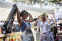 "ROME, ITALY - 3 JULY 2016: (L-R) Gipsy Queens members Aninfa Hokic (31) and Codruta Balteau (24) put on their headscarves as they set up their food stand at the iFest, an alternative music festival  in Rome, Italy, on July 3rd 2016.<br /> <br /> The Gipsy Queens are a travelling catering business founded by Roma women in Rome.<br /> <br /> In 2015 Arci Solidarietà, an independent association for the promotion of social development, launched the ""Tavolo delle donne rom"" (Round table of Roma women) to both incentivise the process of integration of Roma in the city of Rome and to strengthen the Roma women's self-esteem in the context of a culture tied to patriarchal models. The ""Gipsy Queens"" project was founded by ten Roma women in July 2015 after an event organised together with Arci Solidarietà in the Candoni Roma camp in the Magliana, a neighbourhood in the South-West periphery of Rome, during which people were invited to dance and eat Roma cuisine. The goal of the Gipsy Queen travelling catering business is to support equal opportunities and female entrepreneurship among Roma women, who are often relegated to the roles of wives and mothers."
