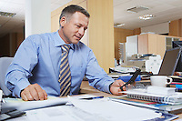 Businessman dialling cell phone at desk