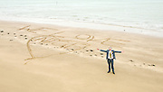 UKIP 2015 Spring Conference at the Winter Gardens Margate, Great Britain <br /> 28th February 2015 <br /> <br /> <br /> Sam Gould <br /> UKIP PPC Caerphily <br /> writing a message to Nigel Farage on the beach outside the conference venue. <br /> <br /> <br /> <br /> Photograph by Elliott Franks <br /> Image licensed to Elliott Franks Photography Services