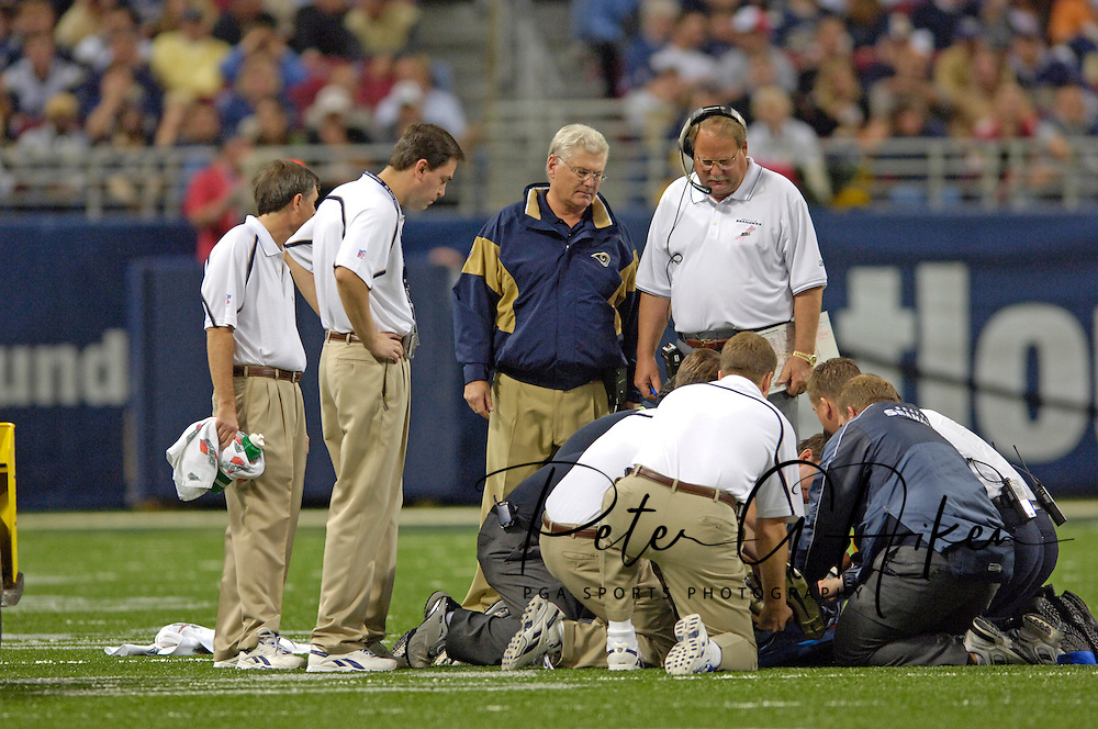 Seattle and St. Louis trainers attend to injured Seahawk Michael Boulware as Seattle head coach Mike Holmgren (R) and St. Louis head coach Mike Martz (L) look on in the first half at the Edward Jones Dome in St. Louis, Missouri on October 9, 2005.  Seattle defeated St. Louis 37-31.