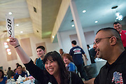 Jennifer Ali, left, places her bid during the live auction during the Milpitas Chamber of Commerce Crab Feed at Napredak Hall in San Jose, California, on March 6, 2015. (Stan Olszewski/SOSKIphoto)