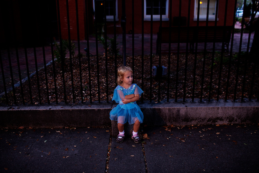 Madelyn Avery Eich, 2, dressed in a blue princess dress, sits by a fence next to The Bier Garden in Portsmouth, Virginia on Saturday, September 18, 2010.