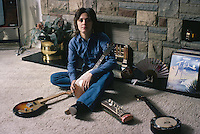 American glam rock singer and bassist Suzi Quatro with a collection of string instruments, circa 1975. On the right is a copy of ZZ Top's album 'Tejas'. (