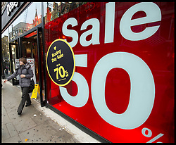 A customer leaves a store with a 70% sale on on a  busy Oxford Street in Central London as bargain hunters shop in the  Boxing Day Sales, Monday December 26, 2011. Photo By Andrew Parsons/i-Images