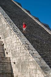 Mexico, Yucatan, Chichen Itza, El Castillo Pyramid, woman climbing steep steps of Mayan ruin