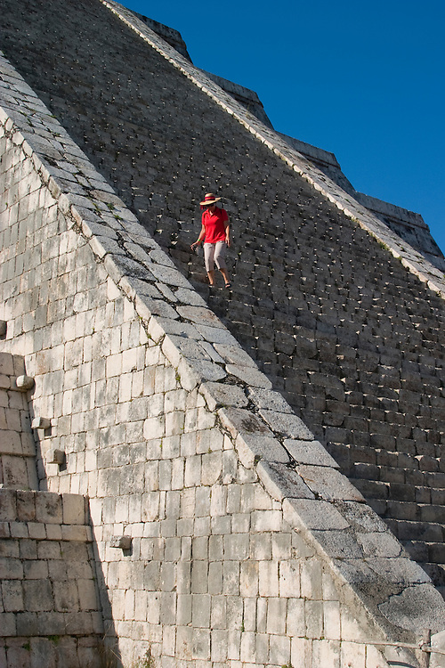 Mexico, Yucatan, Chichen Itza, El Castillo Pyramid, woman climbing steep steps of Mayan ruin