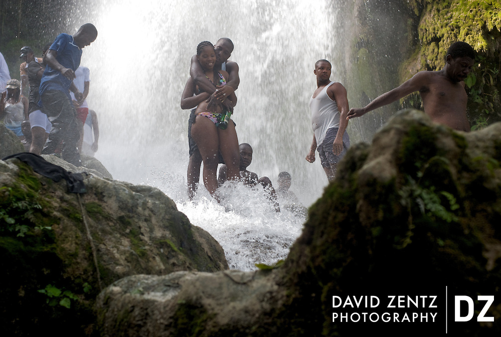 Haitian youth stand beneath the cleansing waters of Saut D'eau, in Haiti, during the annual voodoo pilgrimage there in July