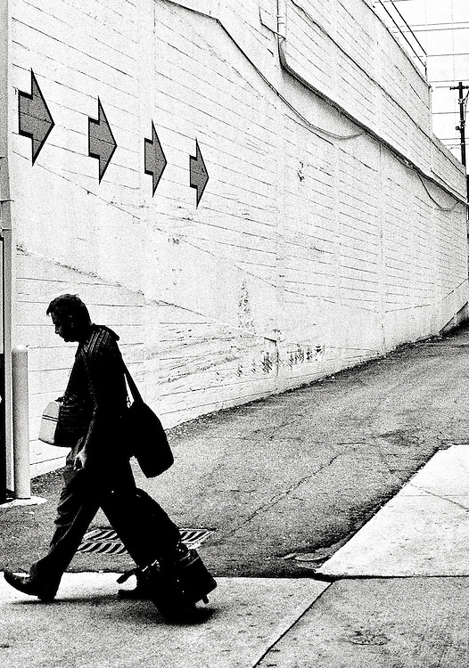 Black and white image of a man with a suitcase walking past a brick wall with arrows painted on it.