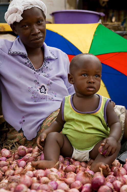 A mother and baby selling onions in the market place, Kalerwe market, Kampala, Uganda.