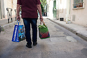 Passerby with shopping bags along a street in Arles, July 6, 2016. © Carlo Cerchioli