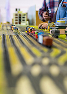 Hicksville, New York, USA. February 22, 2015. Members of a model train club adjust Freight Office and tracks layout scene at Model Train Exhibit hosted by Trainville Hobby Depot at the Broadway Mall, including an N Scale layout, the Long Island HOTrack train club HO scale model train portable modular layout, and Long Island Traction Society O Gauge Trolleys. Donations were accepted at exhibit to support the Nassau County Empire State Games for the Physically Challenged.