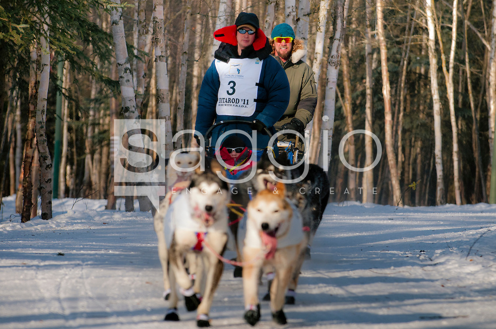 Musher Ray Redington Jr. and Iditarider Branden Bond stroll along the Chester Creek Trail during the 2011 Ceremonial Start.